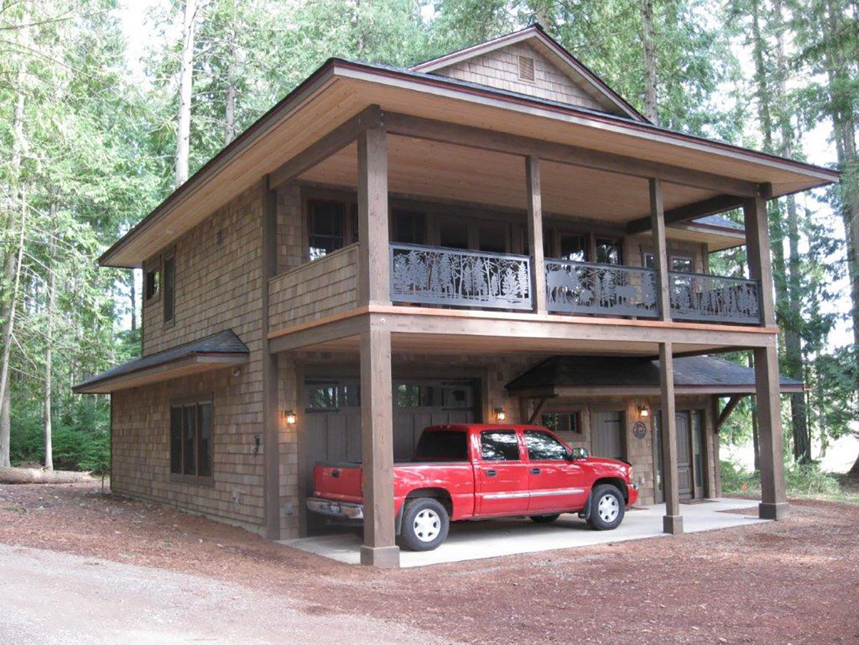 Custom home by Sandpoint Builders in North Idaho, exterior with covered porch and custom iron railing